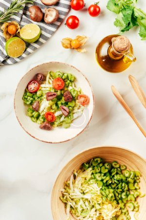 Photo for Top view of salad, cabbage and celery in bowls with bottle of oil, cherry tomatoes, limes and mushrooms - Royalty Free Image