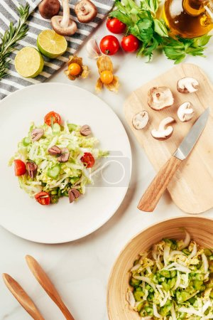 Photo for Salad, cabbage and celery in plate with bottle of oil, cherry tomatoes, limes and mushrooms on cutting board - Royalty Free Image
