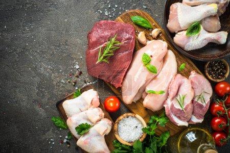 Photo pour Assortiment de viandes fraîches. Boeuf, porc, filet de poulet, ailes et pilons. Table en pierre sombre vue du dessus . - image libre de droit