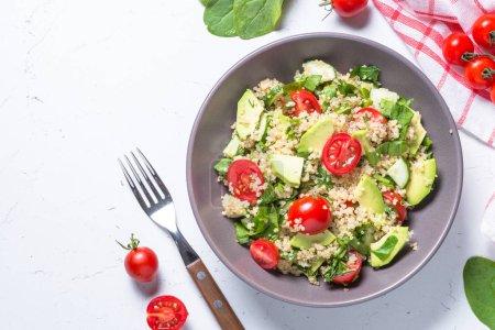Foto de Comida vegana. Ensalada de quinoa con espinacas, el aguacate y el tomate en fondo blanco. Vista superior con espacio de copia. - Imagen libre de derechos