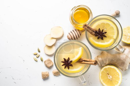 Photo for Hot Ginger tea in glass mug with lemon, honey and spices at white. Healing tea. Top view copy space. - Royalty Free Image