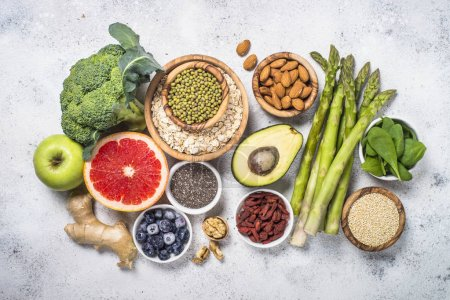 Photo for Superfoods on light stone background. Organic food and healthy vegan food. Legumes, nuts, seeds, avocado and green peas, asparagus. Top view. - Royalty Free Image