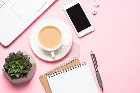 Photo pour Lieu de travail féminin sur bureau rose. Ordinateur portable, bloc-notes, smartphone, tasse à café et cactus. Image de pose plate . - image libre de droit