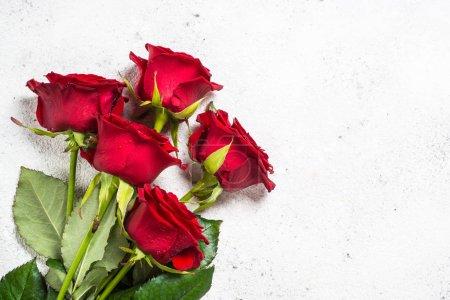 Rote Rosen Blumenstrauß auf weißem Hintergrund von oben.