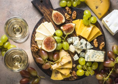 Photo for Cheese plate with grapes, figs and nuts on stone table. Delicatessen food. Top view with copy space. - Royalty Free Image