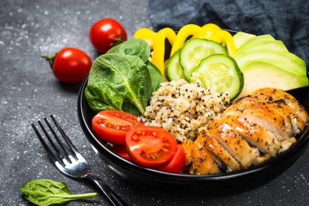 Photo for Buddha bowl on black. Healthy salad from quinoa, chicken, spinach, avocado and tomatoes. Top view. - Royalty Free Image