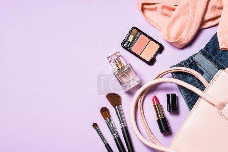 Photo pour Femme plat fond de mode laïc avec tissu, accerrories et cosmétiques. Vue du dessus sur fond violet, espace de copie . - image libre de droit