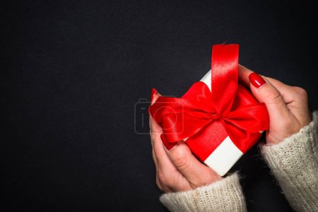 Photo for Woman giving a present on black background. Flat lay image with copy space. - Royalty Free Image