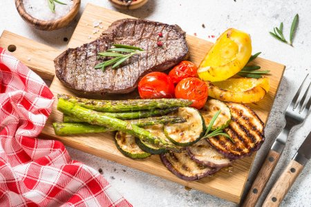 Photo for Grill menu. Beef steak grilled with vegetables on white stone table. - Royalty Free Image