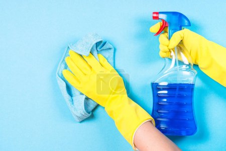 Photo for Cleaning concept. Woman cleaning blue wall with microfiber rag and cleaning spray. - Royalty Free Image