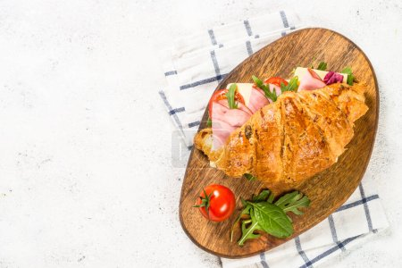 Photo for Croissant sandwich with ham, cheese and vegetables on wooden cutting board. Top view with copy space on white stone table. - Royalty Free Image