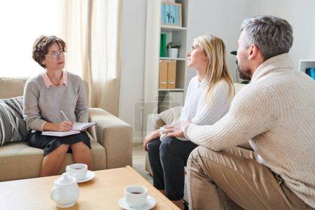 Photo pour Couples mariés tristes avec de graves problèmes dans la relation visitant des psychiatres et partageant leurs souffrances et sentiments à la session de thérapie - image libre de droit