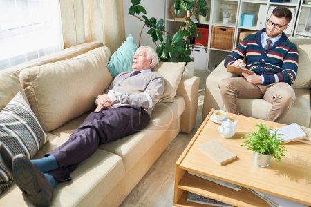 Photo pour Vieil homme déprimé dans le pantalon et le cardigan se trouvant sur le sofa confortable et racontant ses souffrances pour rétrécir qui gardant des disques pendant la session - image libre de droit