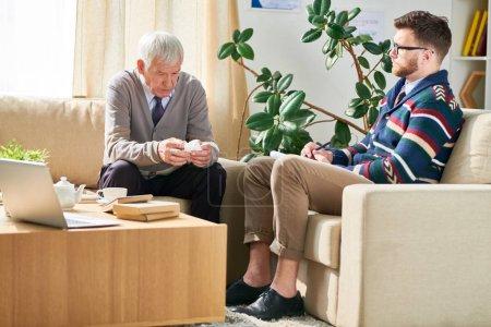 Photo pour Homme aîné sérieux avec la serviette s'asseyant sur le sofa confortable et partageant ses souffrances avec le psychiatre rétrécissant et concentré analysant des mots du patient - image libre de droit