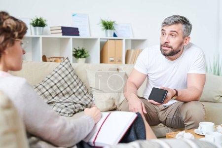 Photo pour Homme barbu et barbu émotif furieux s'asseyant sur le sofa avec des coussins et montrant la vidéo de l'adultère de femmes tout en partageant ses souffrances avec le psychologue - image libre de droit