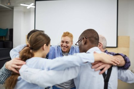 Photo for Group of people hugging all together during therapy session in support meeting, copy space - Royalty Free Image