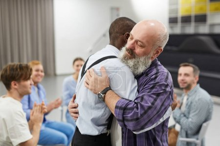 Photo for Side view  portrait of senior man hugging psychologist during therapy session in support group, copy space - Royalty Free Image