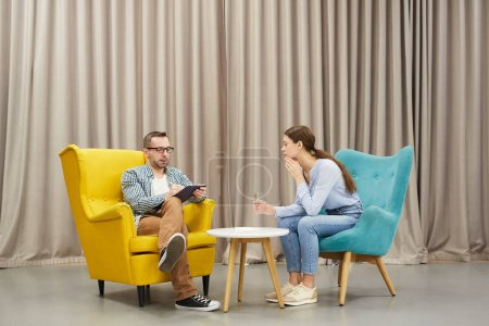 Photo for Full length portrait of young woman talking to mature psychologist in therapy session sitting on design chairs against drapery, copy space - Royalty Free Image