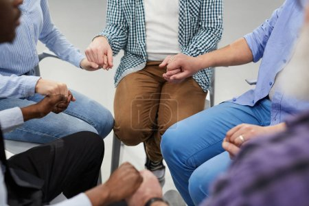 Photo for High angle close up of people holding hands sitting in circle during therapy session in support group, copy space - Royalty Free Image