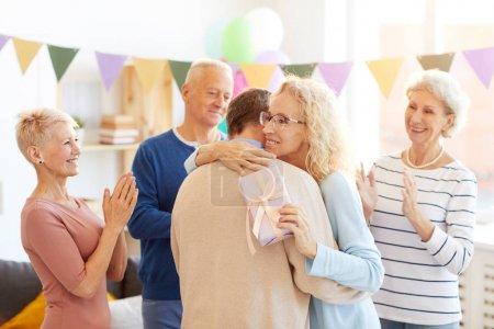 Photo pour Positif attrayant dame mature dans des lunettes debout dans le salon décoré avec guirlande et étreinte ami à la fête d'anniversaire tandis que les femmes excitées et l'homme applaudissant pendant les félicitations . - image libre de droit