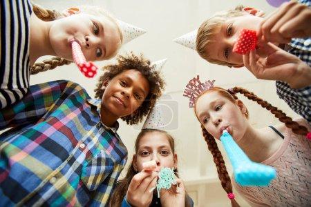 Photo pour Vue à angle bas à plusieurs groupes ethniques d'enfants soufflant des cornes de fête à la caméra et s'amusant - image libre de droit