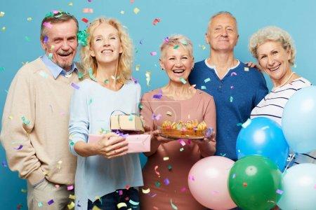 Photo pour Groupe d'amis matures heureux excités en tenue décontractée pleurant de joie à la fête d'anniversaire tout en confettis tomber - image libre de droit
