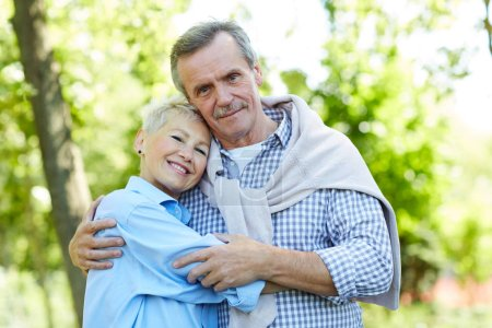 Photo for Waist up portrait of happy senior couple embracing and looking at camera while enjoying walk in Summer park, copy space - Royalty Free Image