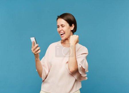 Jeune femme extatique regardant l'écran du smartphone tout en exprimant la joie dans l'isolement