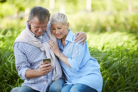 Photo for Portrait of loving senior couple looking at smartphone screen while enjoying date in park, copy space - Royalty Free Image