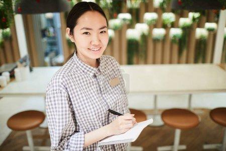 Photo pour Portrait grand angle de serveuse asiatique souriante regardant la caméra tout en prenant l'ordre dans le café, copier l'espace - image libre de droit