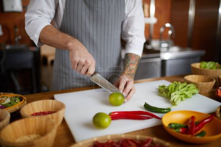 Photo for Close up of unrecognizable chef cutting limes and hot pepper while cooking spicy Asian food in restaurant kitchen, copy space - Royalty Free Image