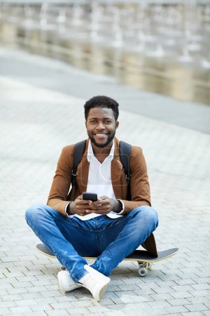 Photo for Full length portrait of contemporary African-American man using smartphone and smiling at camera while sitting cross legged on skateboard outdoors, copy space - Royalty Free Image