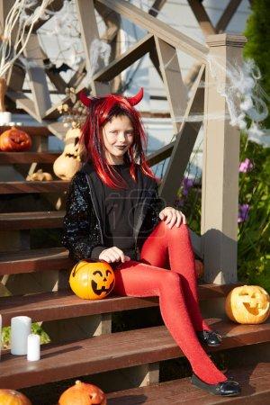 Retrato de larga duración de la adolescente feliz vestido de Halloween posando sentado en el porche decorado al aire libre
