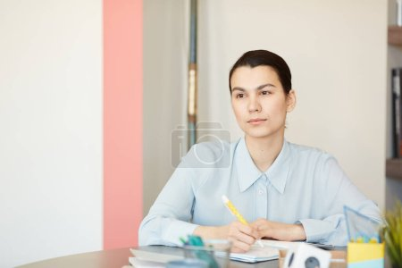 Photo for Beautiful young adult Caucasian woman sitting alone at office desk making notes in notebook, horizontal portrait - Royalty Free Image