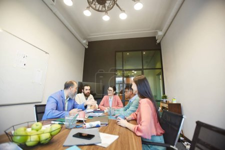 Photo for Group of stylish office workers sitting together in modern office board room doing brainstorming, copy space - Royalty Free Image