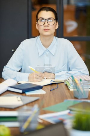 Photo for Modern young businesswoman wearing stylish eyeglasses sitting at table with lots of notebooks on it making notes, looking at camera - Royalty Free Image