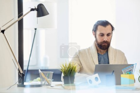 Photo for Young adult Caucasian man with beard on face wearing comfortable outfit sitting at office desk working on laptop - Royalty Free Image