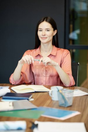 Photo for Vertical medium portrait of young Caucasian woman sitting alone at office desk holding pen looking at camera smiling - Royalty Free Image