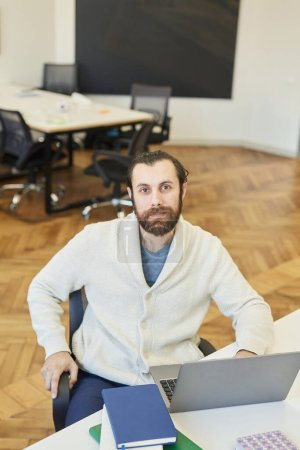 Photo for Vertical high angle portrait of modern young Caucasian man with beard on face wearing comfortable outfit sitting at office desk, looking at camera - Royalty Free Image