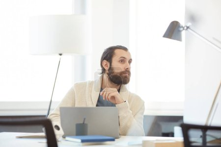 Photo for Young bearded man being interrupted of his work on computer listening to his coworker, horizontal portrait - Royalty Free Image