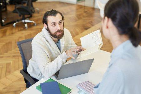 Photo pour Jeune homme assis au bureau partageant ses idées à un collègue méconnaissable, plan horizontal grand angle - image libre de droit