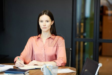 Photo for Horizontal medium portrait of beautiful young Caucasian woman sitting alone at office desk looking at camera - Royalty Free Image