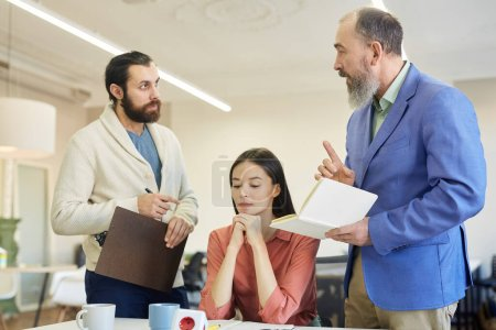 Photo for Two bearded men and young woman having dispute during business meeting, horizontal shot - Royalty Free Image