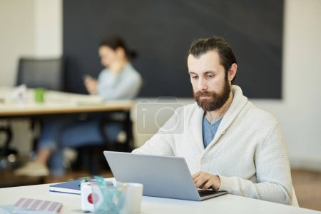 Photo for Handsome young man with beard on face sitting at office table working on his laptop with serious facial expression - Royalty Free Image
