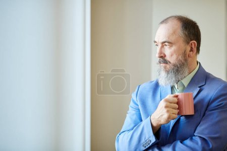 Photo for Stylish senior man with beard on face wearing blue suit holding cup of coffee looking out of window, copy space - Royalty Free Image