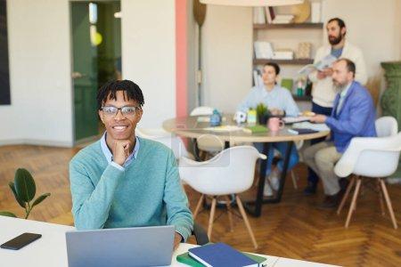 Photo pour Jeune homme afro-américain assis au bureau avec un ordinateur portable souriant à la caméra, ses collègues travaillant derrière lui - image libre de droit