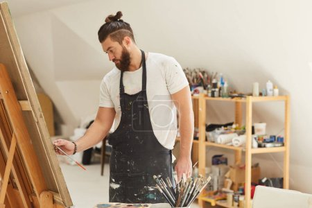 Photo for Waist up portrait of contemporary bearded artist painting picture on easel while working in spacious art studio, copy space - Royalty Free Image