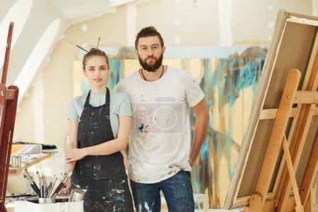 Photo pour Portrait taille haute de couple adulte créatif regardant la caméra tout en se tenant dans l'intérieur du studio d'art, espace de copie - image libre de droit