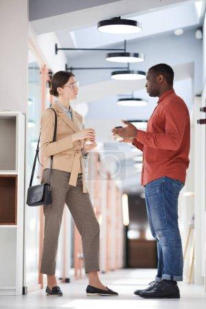 Foto de Retrato de vista lateral de longitud completa de dos personas de negocios contemporáneos charlando mientras están de pie en la sala de oficinas - Imagen libre de derechos