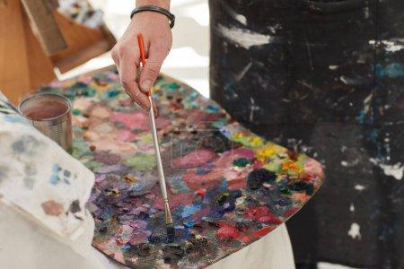 Photo pour Gros plan d'un artiste masculin méconnaissable mélangeant peinture sur palette tout en peignant dans un atelier d'art, espace de copie - image libre de droit